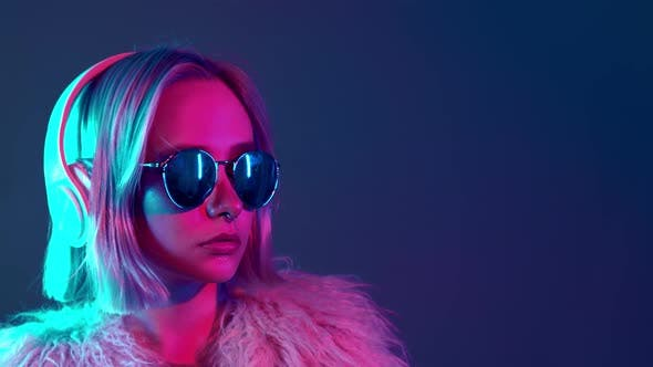 Thumbnail for Glamorous Hipster Teenager in Sunglasses and Furry Coat Listening To Music with Headphones, Portrait