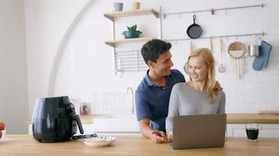Couple Using Laptop in Kitchen