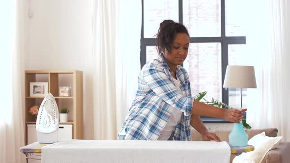 Thumbnail for African American Woman Ironing Bed Linen at Home 8