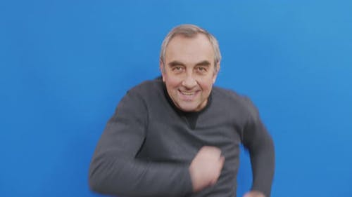 Happy Fun Mature Man Rejoices and Dances Isolated on Blue Background in Studio. People Emotions