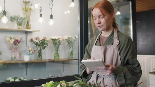 Female Florist Doing Inventory In Flower Shop