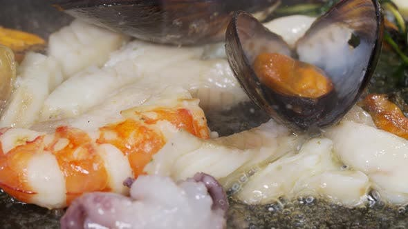 Chef Prepares Prawns with Fire in Frying Pan in Restaurant Kitchen. Slow Motion. Seafood Dish Cooked
