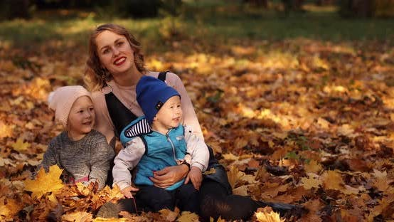 Thumbnail for Gorgeous Young Mother with Two Kids Enjoying Sunny Autumn Day on the Foliage