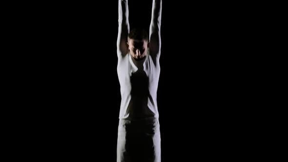 Thumbnail for Young Handsome Male Acrobat Gymnast in White Clothes on a Black Background Makes Jumps and Shows