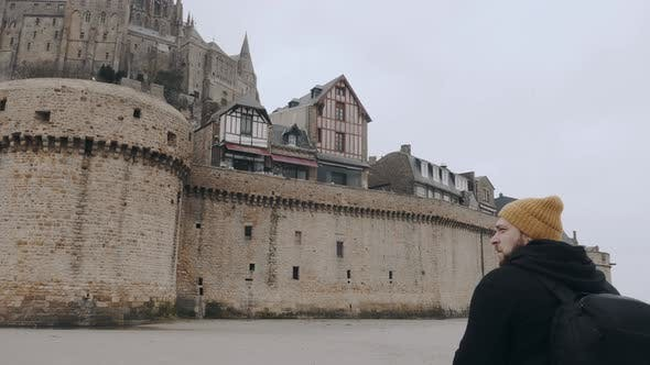 Thumbnail for Camera Moves Around Happy Excited Tourist Man with Backpack Stunned By Epic Mont Saint Michel Castle