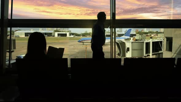 Woman Reading a Book in Airport Terminal at Sunset.