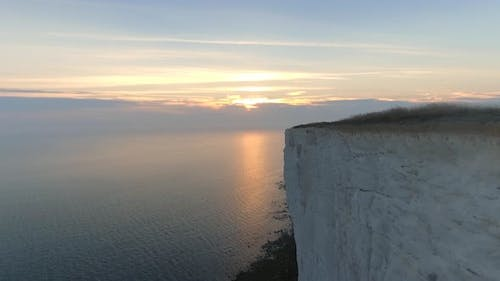 Low and Fast Flight Over a Steep Cliff Edge Towards the Setting Sun