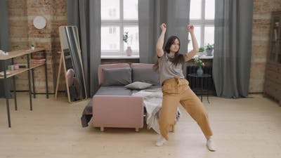 Energetic Young Woman Dancing at Home