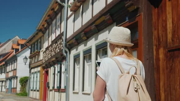 Thumbnail for A Woman with a Smartphone in Her Hands Is Walking Along the Narrow Street of the Old German Town