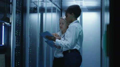 Zwei Frauen arbeiten in einem Rechenzentrum mit Reihen von Server-Racks