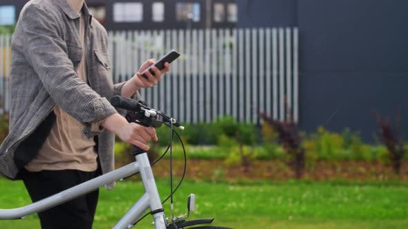 Thumbnail for Young Man with Bicycle and Smartphone in City