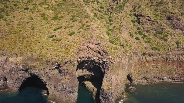 Thumbnail for Aerial View on White Pleasure Boat with People on Board Anchored Near the Caves of Lipari Island in