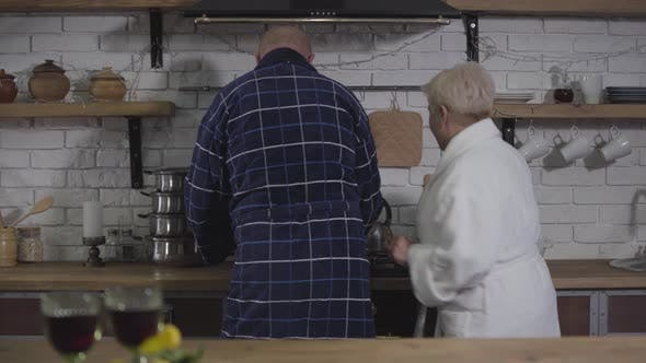 Thumbnail for Senior kaukasischen Ehemann und Ehefrau Kochen in der Küche am Morgen. Frau verlassen und setzen