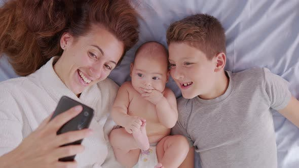 Thumbnail for Happy Mother with Her Kids Are Making a Selfie or Video Call To Father or Relatives in a Bed