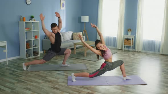 Woman Instructs Man in Stretching