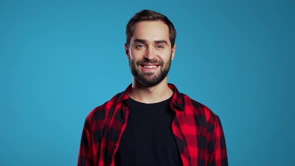 Thumbnail for Handsome European Man with Trendy Beard in Red Plaid Shirt on Blue Studio