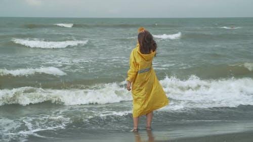 Woman In Raincoat Standing In Waving Sea