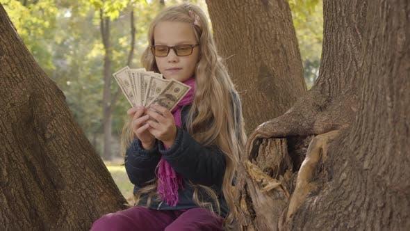 Thumbnail for Junge blond kaukasische Mädchen in photochrome Gläser Zählen Geld und Denken Als Sitzen