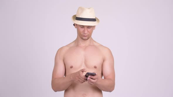 Thumbnail for Happy Muscular Tourist Man Smiling While Using Phone Shirtless