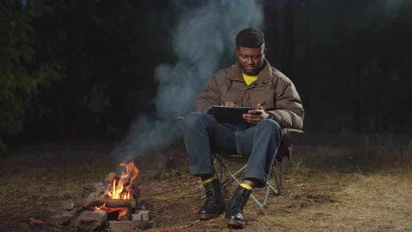 African Traveler Working on Tablet Pc By Campfire