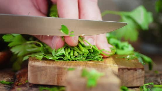 The Hand of a Man with a Knife Cut Fresh Parsley on a Cutting Board.