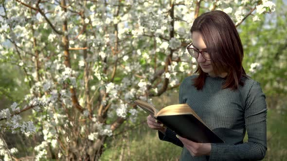 Young Woman on Nature with a Book in His Hands. A Girl Reads a Book While Standing Against a
