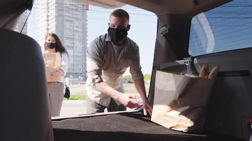 Man in Face Mask Putting Groceries into Trunk of Car