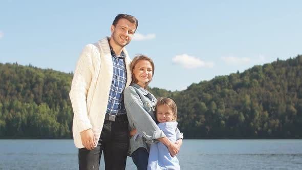 Thumbnail for Happy Family Looking at Camera While Posing on Pier at Quiet Lake