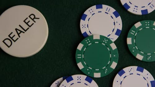 Rotating shot of poker cards and poker chips on a green felt surface - POKER 042