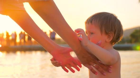 Cover Image for Concept of Love Family Trust. Close Up of Kid Giving Hand To Mother. Hands of Mother and Baby