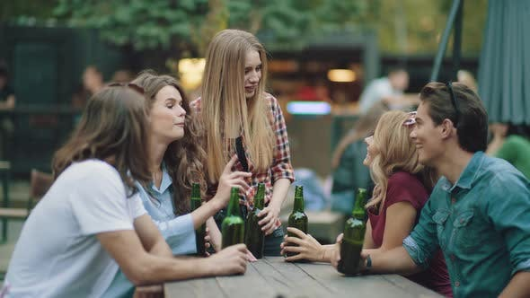 Friends Drinking Beer And Toasting At Outdoor Party