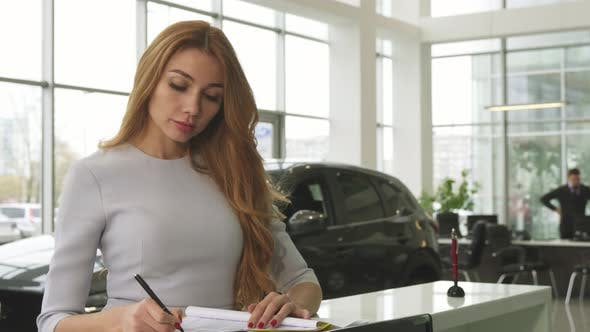 Cover Image for Gorgeous Woman Buying a New Car at the Dealership Smiling To the Camera