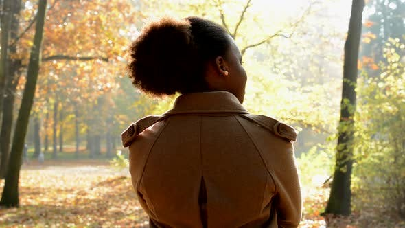 Thumbnail for Young Beautiful Happy African Girl Stands Back Turned in the Woods - Turns and Stare To Camera