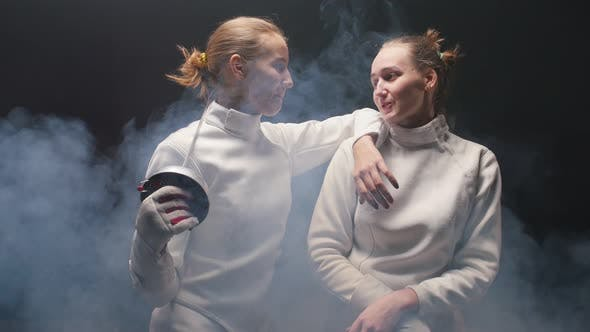 Cover Image for Two Young Women Fencers in White Protective Suits Talking To Each Other - Leaning on the Shoulder of