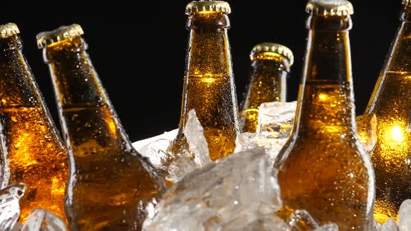 Thumbnail for Condensate Flows Down the Brown Glass of Bottles From Beer, Black Background