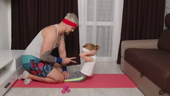 Sportsman Trainer Man Working Out with Child Kid Girl Abs Exercises with Daughter at Home on Mat