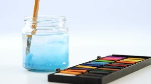 Paintbrush dipping in water