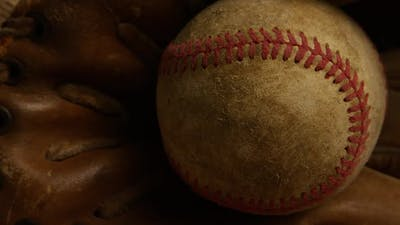 Rotating shot of weathered baseball and baseball glove