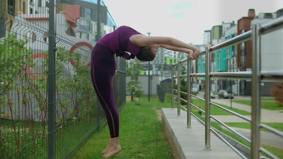 Thumbnail for Athletic Woman Does Stretching Exercises at the Handrails in the Yard of an Apartment Living Complex