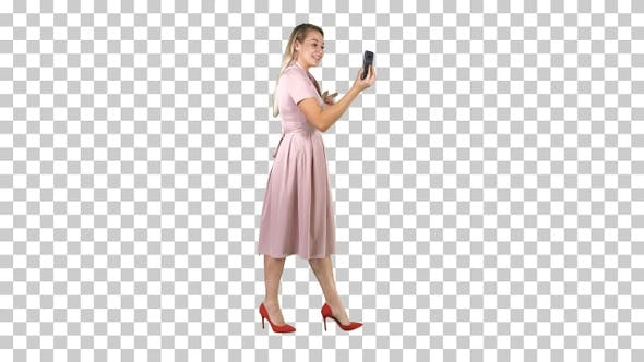 Thumbnail for Young woman in pink holding using smart phone recording video