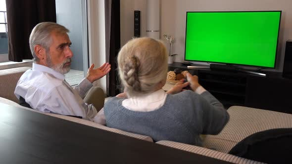 Thumbnail for An Elderly Couple Watches TV with A Green Screen and Fights Over the Remote Control
