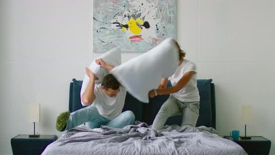 Young Mixed Couple Has a Pillow Fight in Bedroom