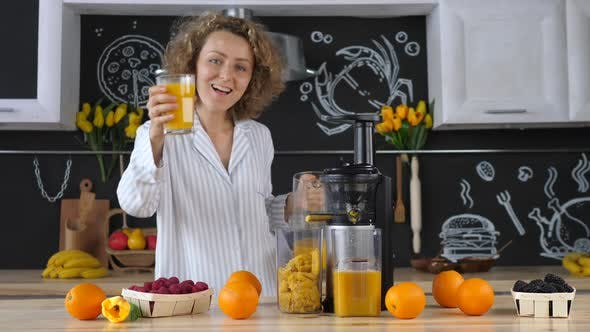 Beautiful Young Woman In Kitchen Squeezing Orange Juice With Juicer