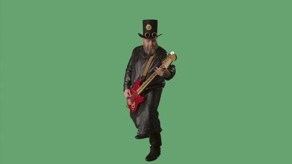 A Bearded Man in a Long Leather Coat and an Irishstyle Hat Plays the Red Guitar