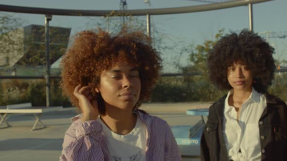 Two Mixed Race Black Woman with Huge Afro Hair Outdoors Watching To the Camera