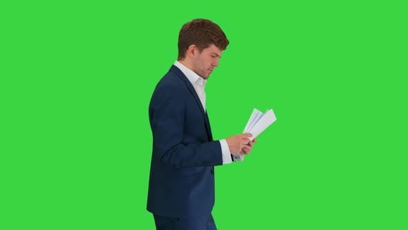 Thumbnail for Serious Businessman Reading Documents or Report While Walking on a Green Screen, Chroma Key.