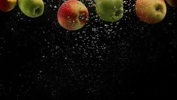Thumbnail for Red and Green Apples Falling in Splash of Water with Air Bubbles Isolated on Black Background