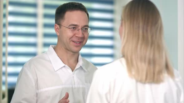 Thumbnail for Smiling Male Doctor in Glasses Talking To Female Nurse