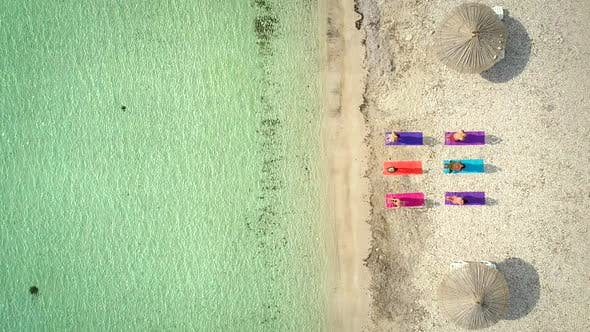 Thumbnail for Aerial view of yoga group on mats on beach with parasols.