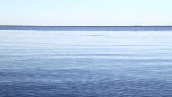 Waves and ripples run on blue water surface